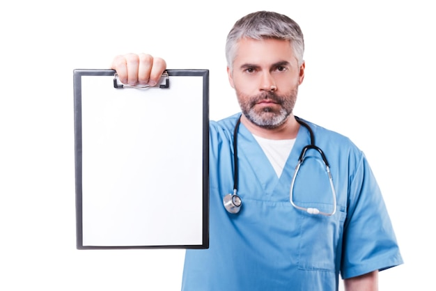 Copy space on his clipboard. confident mature doctor looking at camera and showing clipboard with copy space on it while standing isolated on white