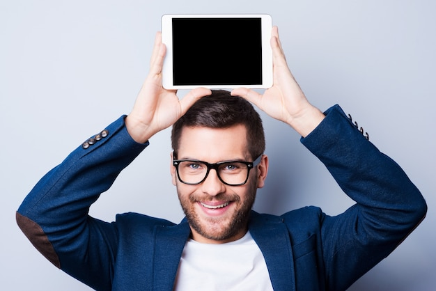 Copy space on his tablet. cheerful young man holding a digital tablet upon his head and smiling while standing against grey background