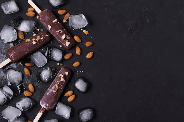 Copia-spazio gelato sul bastone con cubetti di ghiaccio