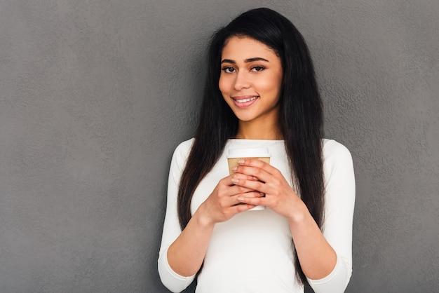 Скопируйте пространство в ее руке. привлекательная молодая африканская женщина, держащая чашку кофе и смотрящая в камеру с улыбкой, стоя на сером фоне