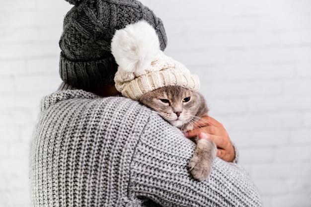 Copy-space мужчина и кошка в меховой шапке