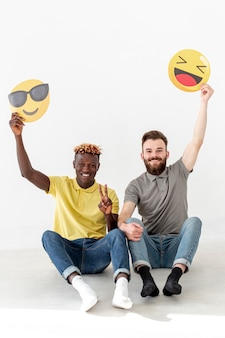 Copy-space male friends sitting on floor and holding emoji