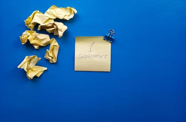 Скопируйте пространство. месяц в году. желтая наклейка. на листе надпись сентябрь. 1 сентября.