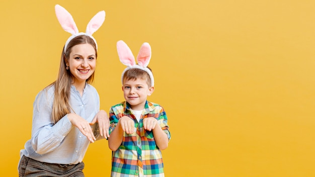 Copy-space мать и сын подражают кролику