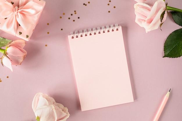 ピンクのバラとギフトボックスが付いた明るいピンクの背景にテキストのスペースメモ帳をコピーします。フラットレイ。上面図。