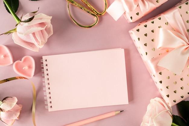 ピンクのバラとギフトボックスが付いた明るいピンクのテーブルに、テキスト用のスペースメモ帳をコピーします。フラットレイ。上面図。