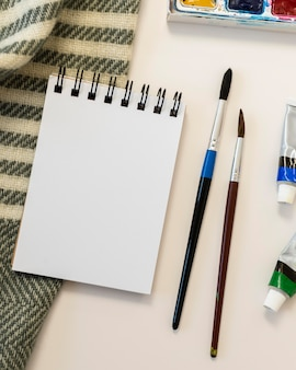 Copy space notepad and paint brushes