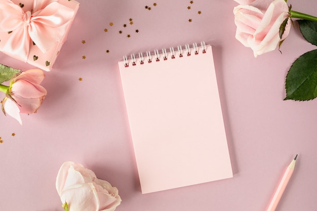 Copy space notepad for your text on a light pink background with pink roses and gift boxes. flat lay. top view.