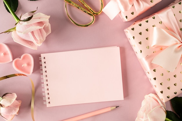 Copy space notepad for your text on a light pink table with pink roses and gift boxes. flat lay. top view.