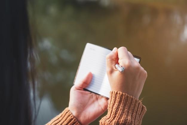 太陽光の背景を持つ白いノートに書き留める女性の手のスペースをコピーします。