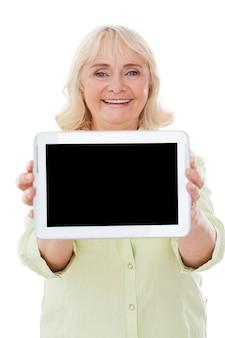 彼女のデジタルタブレットのスペースをコピーします。彼女のデジタルタブレットを表示し、白い背景で隔離に立って笑っている幸せな年配の女性