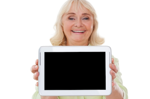 タブレットのスペースをコピーします。陽気な年配の女性がデジタルタブレットを伸ばして、白い背景に孤立して立っている間笑顔