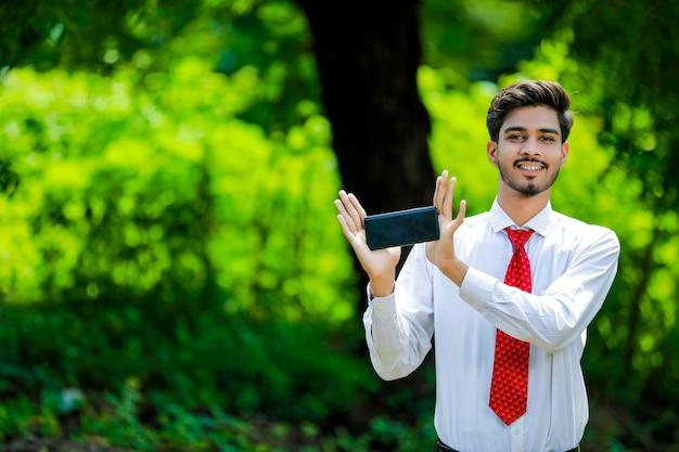 Скопируйте пространство на своем смартфоне. уверенный молодой индийский мужчина показывает свой смартфон