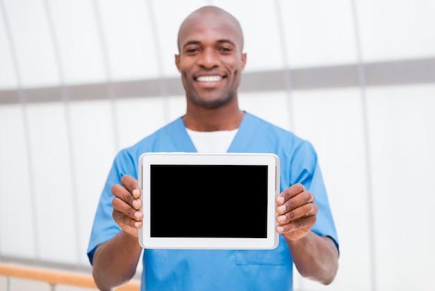 タブレットのスペースをコピーします。彼のデジタルタブレットと笑顔を見せて青い制服を着た陽気な若いアフリカの医者