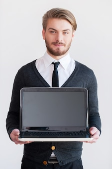 Скопируйте место на мониторе. красивый молодой человек держит ноутбук и улыбается, стоя на сером фоне