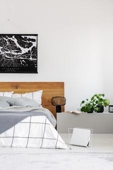 나무 헤드보드가 있는 킹 사이즈 침대가 있는 현대적인 침실에 검은색 지도가 있는 흰색 벽에 공간 복사