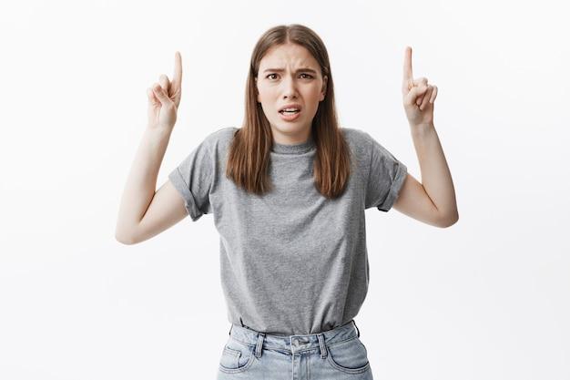 공간을 복사하십시오. 사람들의 감정. 혐오 얼굴 표정으로 회색 셔츠와 청바지에 재미 잘 생긴 갈색 머리 유럽 학생 소녀