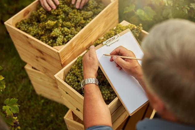 Копировальная фотография человека, пишущего на чистом листе бумаги, стоя возле ящиков с виноградом