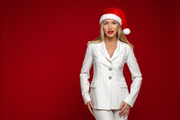 Копировальное фото стильной блондинки в шляпе санта-клауса, смотрящей в камеру. концепция праздника. копировать пространство