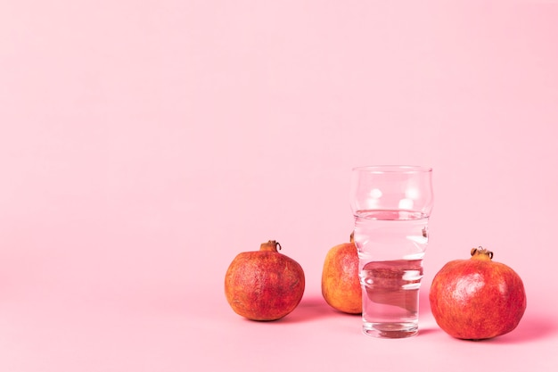Copy space pink background with pomegranate fruit