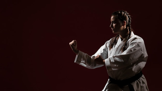 Copy space red background and woman in white karate uniform