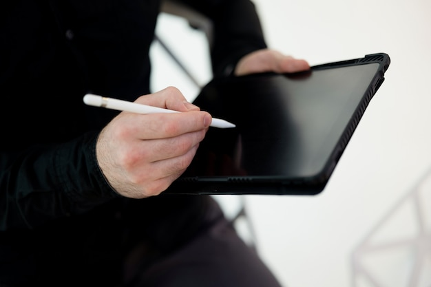 タブレットのスペース画面をコピーします。スタイラスを使用してガジェットに署名する男性の手のショットをクローズアップ。暗い服を着た男のカットビュー。電子請求書に無謀に署名しないでください!金融リテラシーの概念。