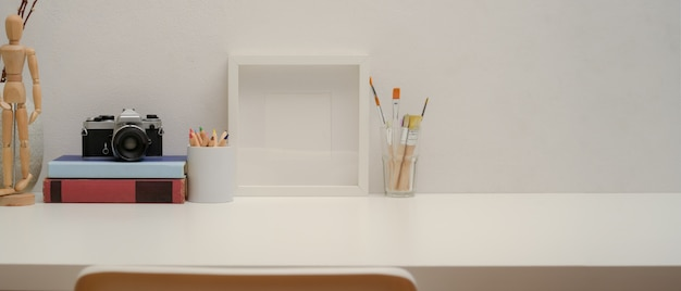 Copy space on study table with mock up frame, painting tools, camera, books on white desk