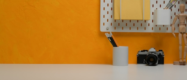 Copy space on stylish workspace with stationery, camera, stationery and shelf on yellow wall