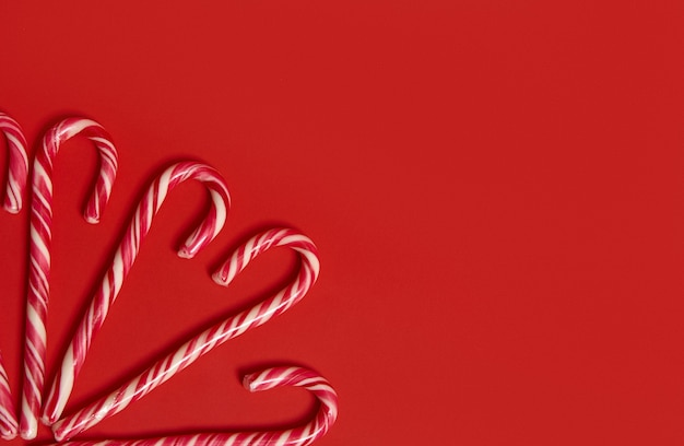 Copy space for text and advertising on red background with sweet christmas candy canes in the corner of the image. high angle view of christmas decoration.