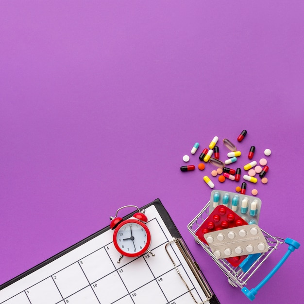 Copy-space toy cart with clock and pills beside