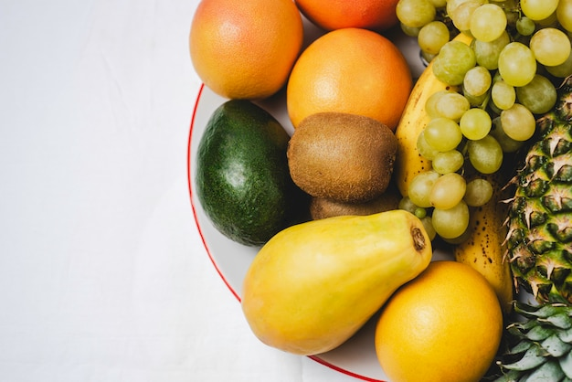 Copy space variety of fresh fruits on a plat over white background.