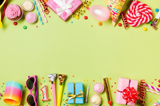 誕生日アイテムと菓子の緑色の背景でコピースペース