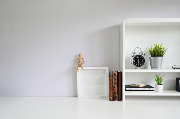 Copy space with books, alarm on white table.