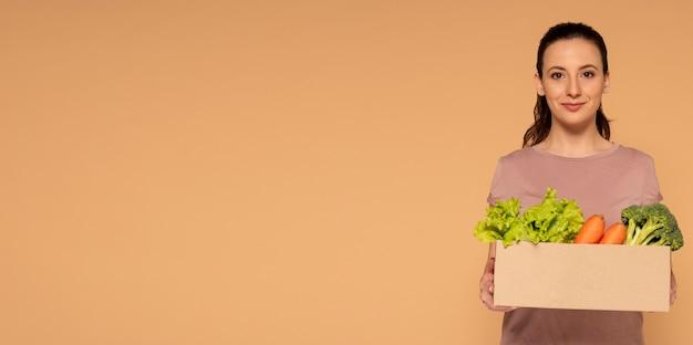 野菜と漫画の箱を保持しているスペースの女性をコピーします。