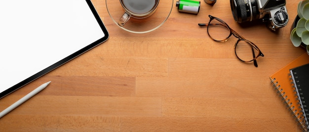 Copy space on wooden table with mock-up tablet, supplies and decoration