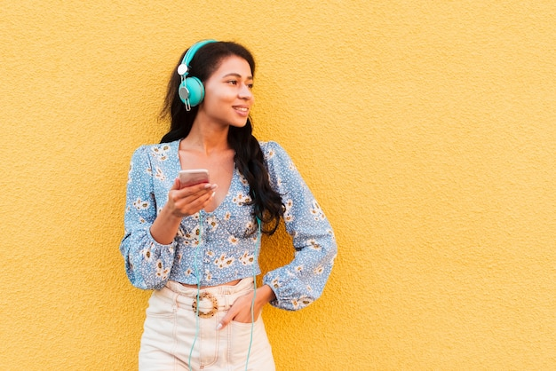 Copy space yellow background with woman and headphones