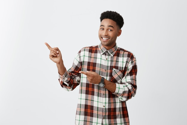 Copy space. young dark-skinned african cheerful guy with afro hairstyle in checkered shirt pointing aside with hands on white wall with happy and excited expression