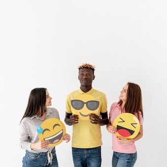 Copy-space young friends holding emoji