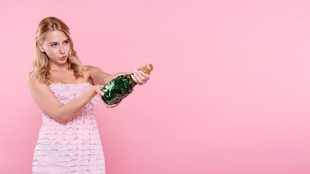 Copy-space young woman popping champagne at party