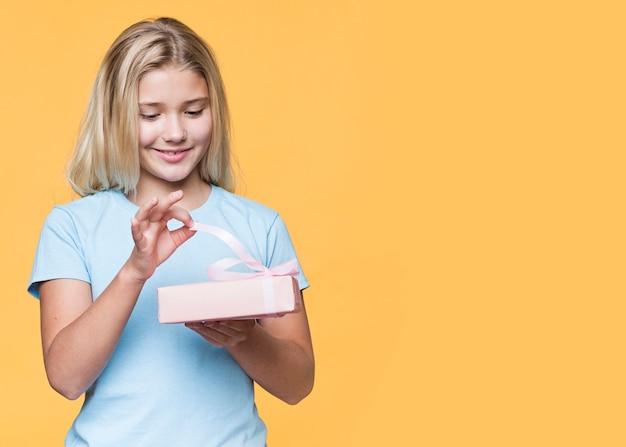 Copy-space девушка, открывающая подарок