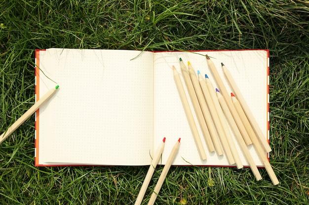 コピーブックと緑の芝生に色鉛筆。創造性