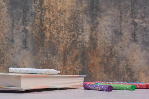 Quaderno e matite colorate sul tavolo bianco.