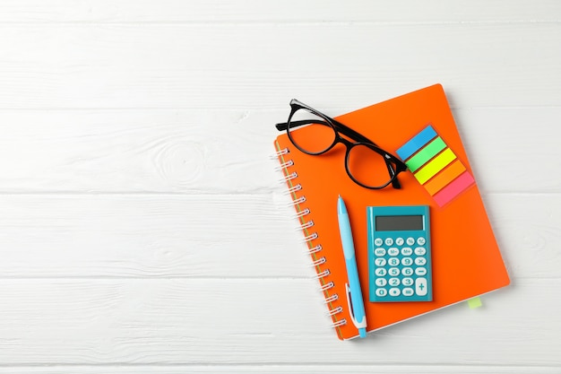 Copybook, glasses, calculator, pen and stickers on wooden, space for text