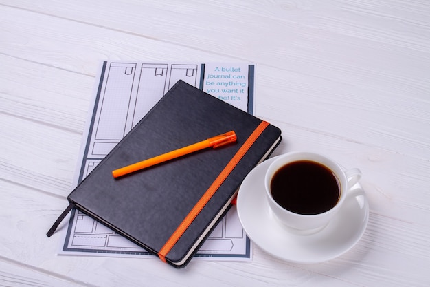 Copybook with pen and cup of coffee.