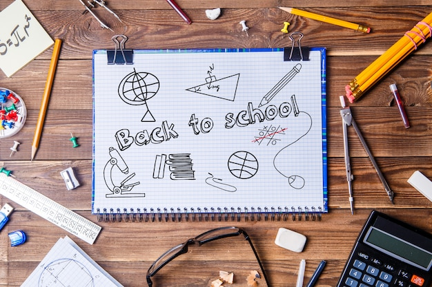 Copybook with text - back to school and student material on wooden table.