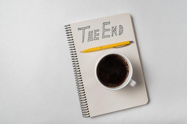 Тетрадь с текстом «конец». блокнот, ручка и чашка кофе на белом фоне.