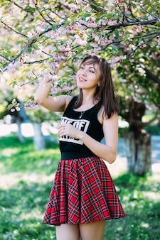 Улыбающиеся женщина трогательно сакуры цветущее дерево и улыбается. женщина на цветущей вишне. концепция весны. copyplace