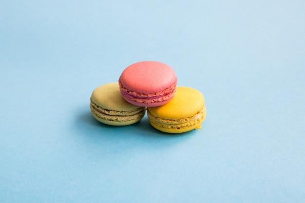 カラフルなマカロン、青の背景にピンク、黄色、緑のマカロン。お菓子、デザート。 copyplace、テキストのための場所。