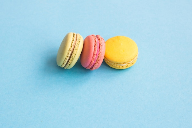 マカロン、青の背景にピンク、黄色、緑のマカロン。明るくカラフルなコンセプト。 copyplace、テキストのための場所。