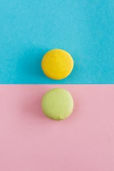 青とピンクの背景にカラフルなマカロン、黄色と緑のマカロンの平面図です。お菓子、デザート。 copyplace、テキストのための場所。